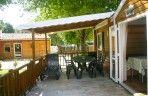 Ruime mobile home met houten gevels en half overdekt terras.
